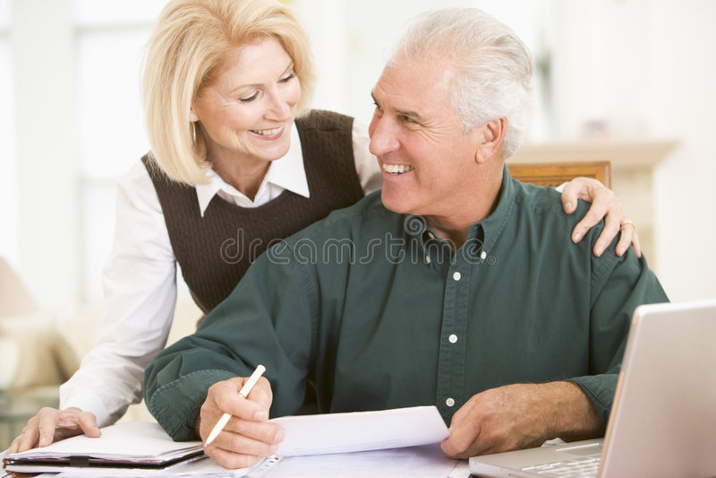 Paar in eetkamer met laptop en administratie stock afbeelding