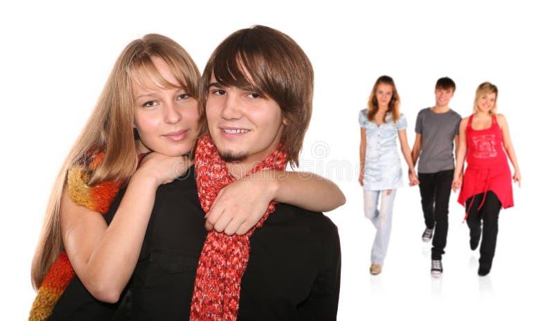 Paar en groep vrienden erachter stock afbeelding
