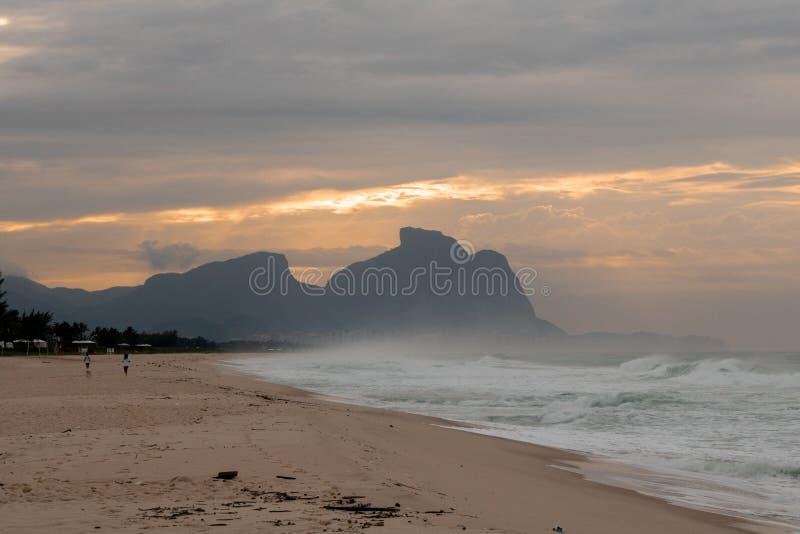 Paar en hond die op het strand van Barra da Tijuca in een mooie dageraad met de steen van Gavea op de achtergrond lopen - Rio de  stock foto