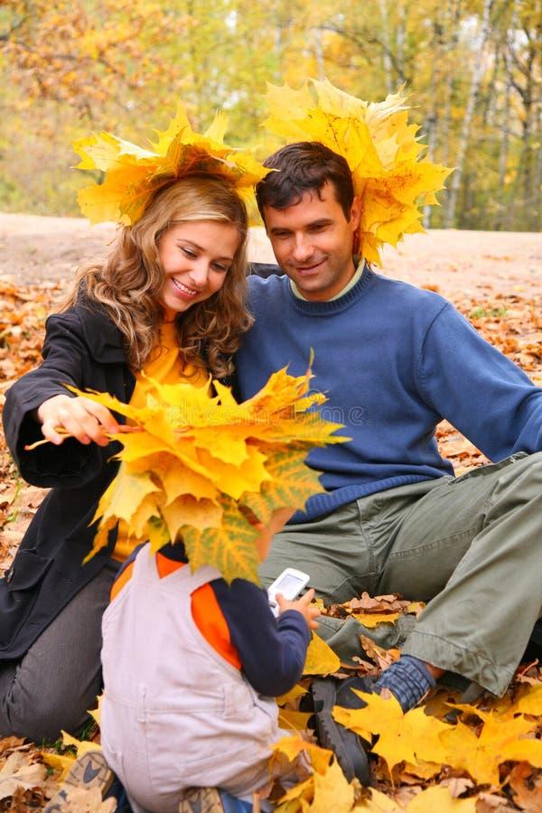 Paar en kind met esdoornbladeren royalty-vrije stock fotografie