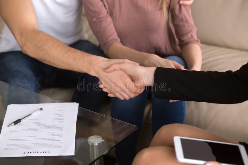 Paar en onderneemster het schudden de handen, makend overeenkomst, het ondertekenen bedriegen stock foto's