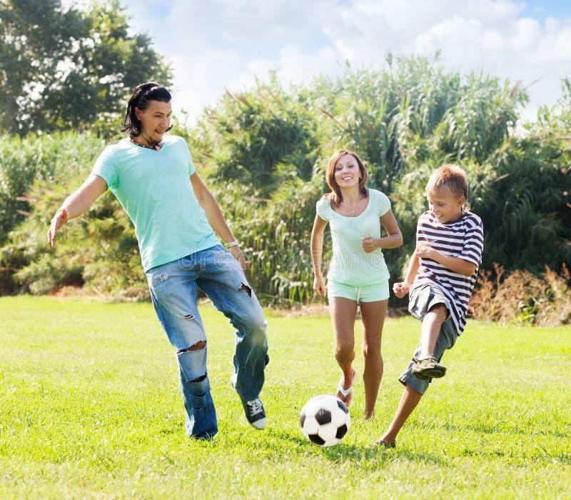 Paar en tiener spelen het op middelbare leeftijd met voetbalbal stock foto