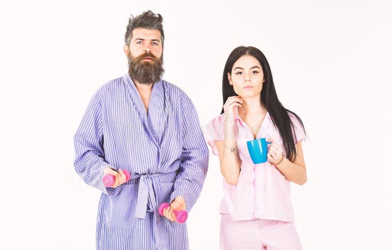 Paar, Familie bietet Quelle der alternativen Energie an Paare in der Liebe im Pyjama, Bademantelstand lokalisiert auf weißem Hint lizenzfreies stockfoto