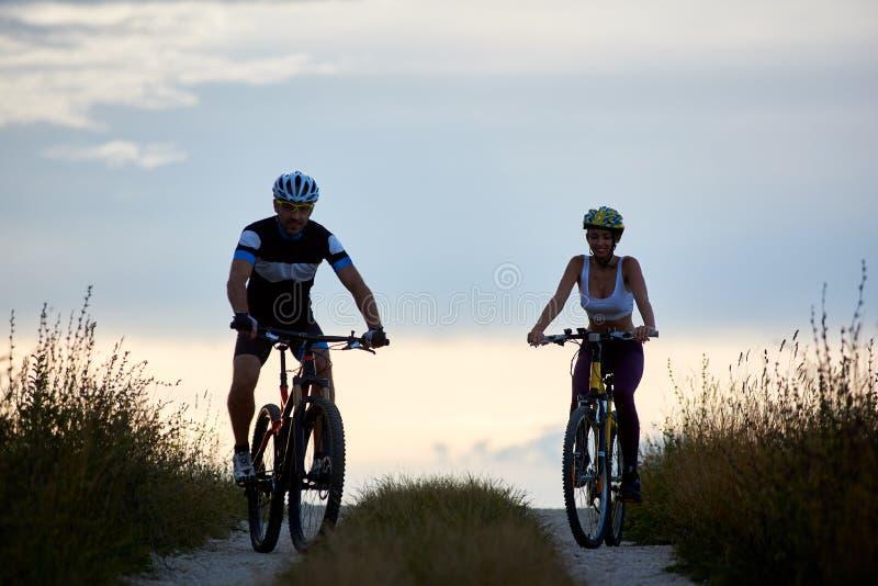 Paar fietser berijdende fietsen bij de landweg Geschikte jongeren die in sportkleding bergaf cirkelen stock foto