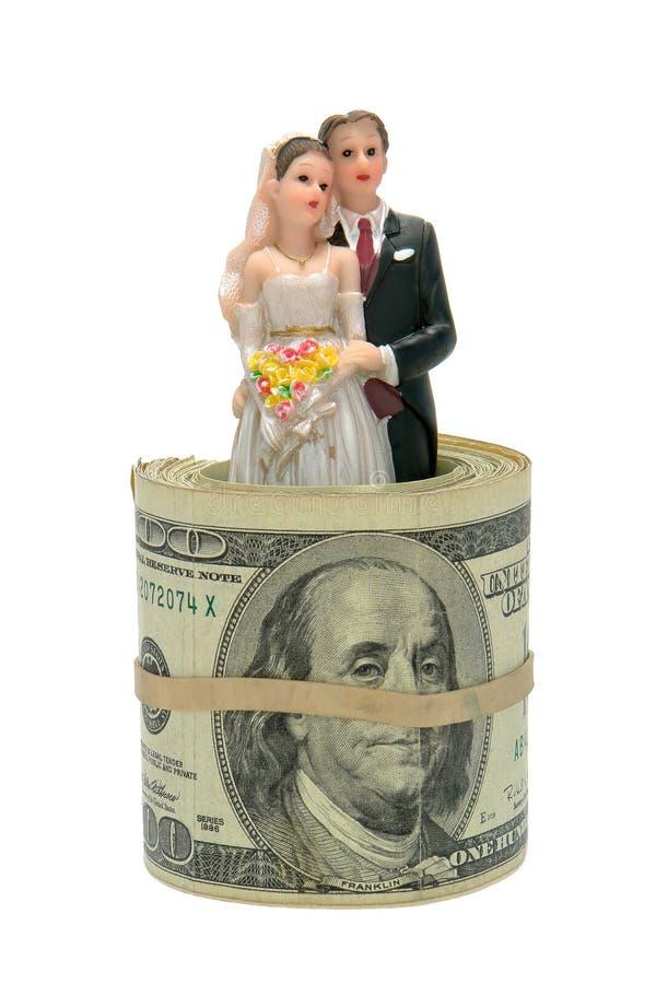 Paar-Figürchen innerhalb der Dollarschein-Rolle stockfoto