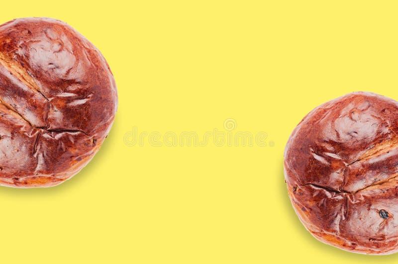 Paar gebakken cirkel suikerachtige bruine broden met rozijnen op gele lijst in keuken met exemplaarruimte voor uw tekst royalty-vrije stock fotografie