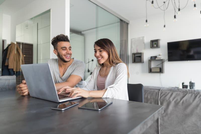 Paar-Gebrauchs-Laptop-Computer, die bei Tisch im modernen Wohnungs-zusammen junger Mann-und Frauen-Brandungs-Internet sitzt stockbilder