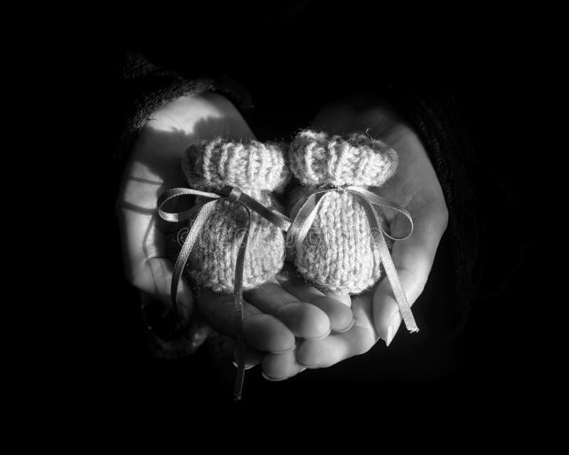 Paar Gebreide Babybuiten in de Hart Gevormde Palmen van een Woma royalty-vrije stock foto's