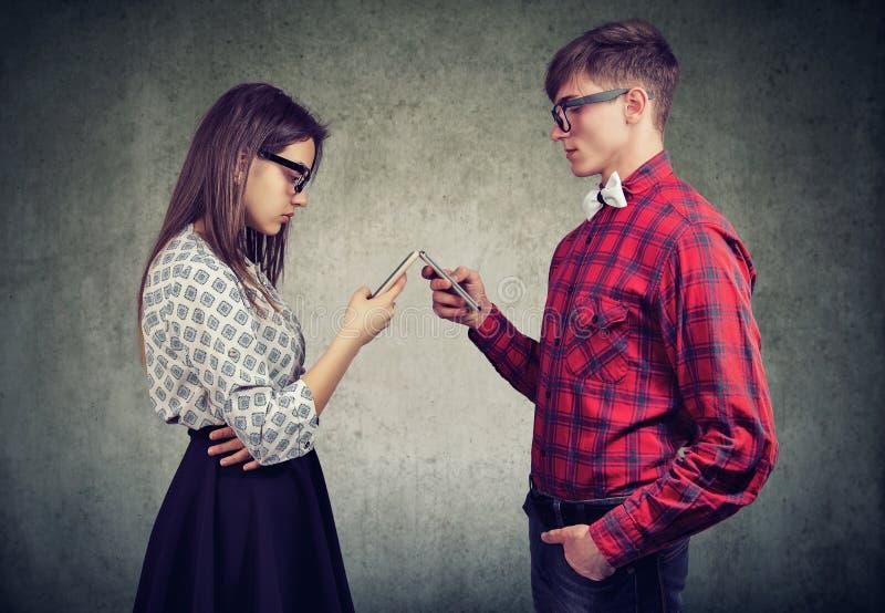 Paar gebruiken smartphones totaal geabsorbeerd in het online leven, sprekend niet aan elkaar, die elkaar onder ogen zien stock fotografie