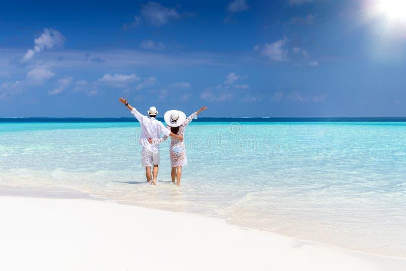 Paar geht hinunter einen tropischen Strand in der weißen Kleidung lizenzfreie stockfotografie