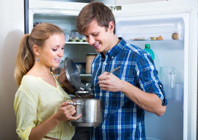 Paar geopende koelkast die voedsel kijken stock afbeeldingen