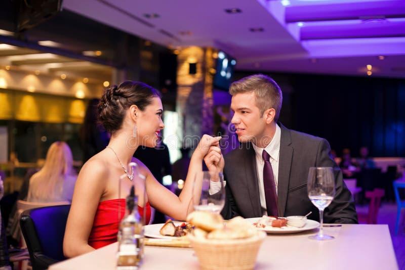 Paar geruilde tederheid bij restaurant royalty-vrije stock afbeeldingen