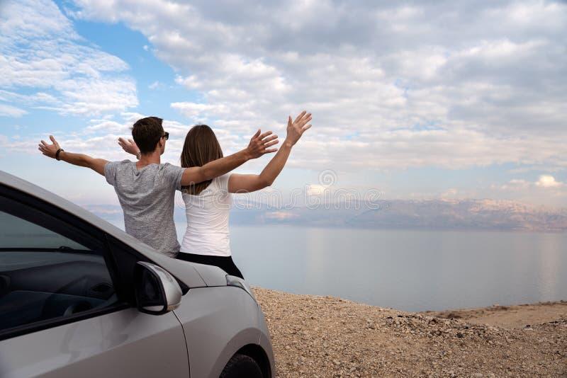 Paar gezet op de motorkap van een gehuurde auto op een wegreis in Isra?l royalty-vrije stock foto