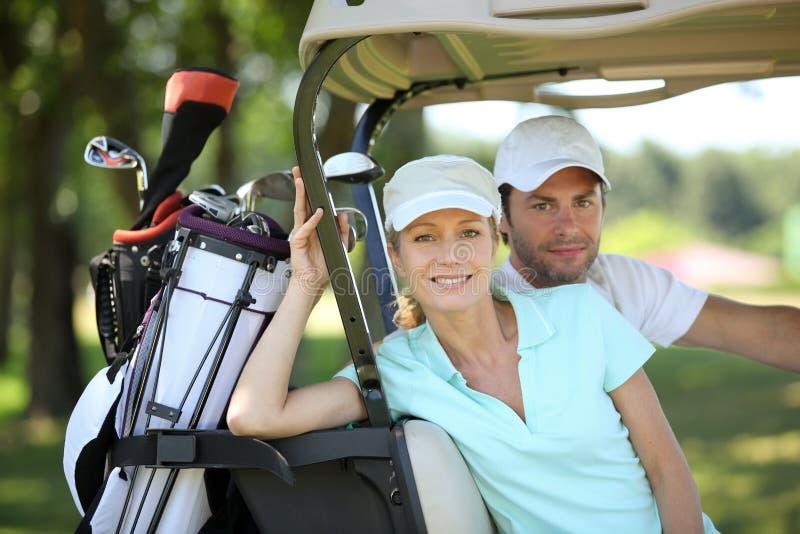 Paar in golfkar stock afbeeldingen