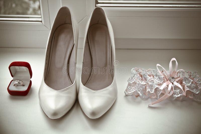 Paar gouden trouwringen, bruids schoenen, kouseband royalty-vrije stock afbeelding