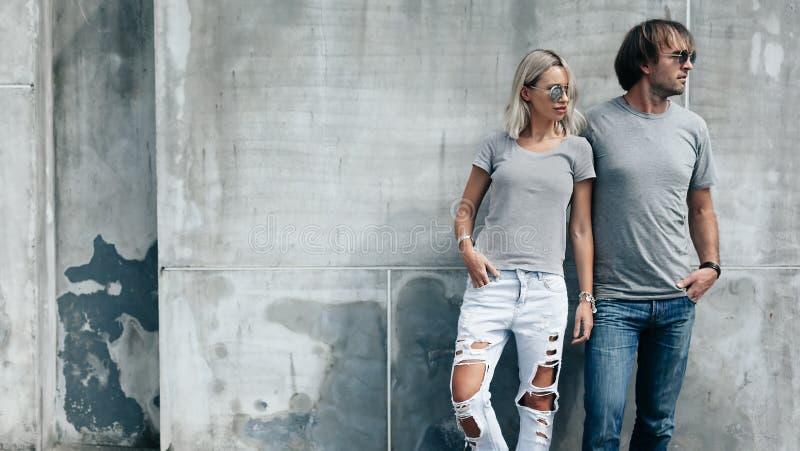 Paar in grijze t-shirt over straatmuur stock foto's