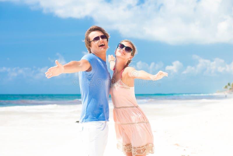 Paar in heldere kleren bij het tropische strand glimlachen stock foto's