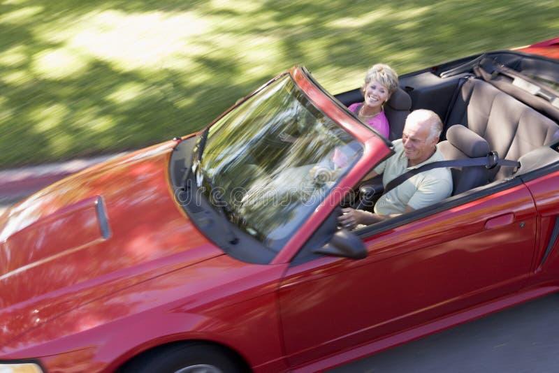 Paar in het convertibele auto glimlachen