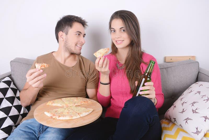 Paar het drinken bier en het eten van pizza stock foto