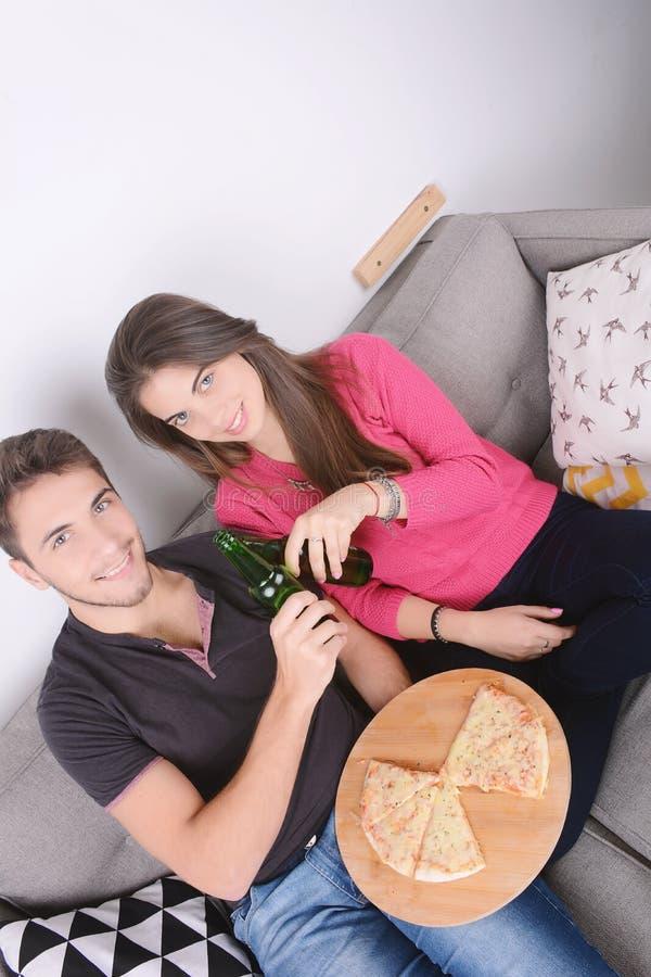 Paar het drinken bier en het eten van pizza royalty-vrije stock afbeeldingen