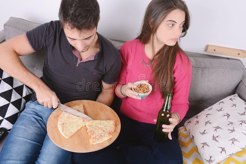 Paar het drinken bier en het eten van pizza stock afbeeldingen