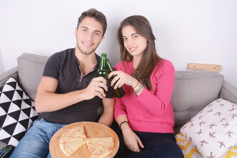 Paar het drinken bier en het eten van pizza royalty-vrije stock fotografie