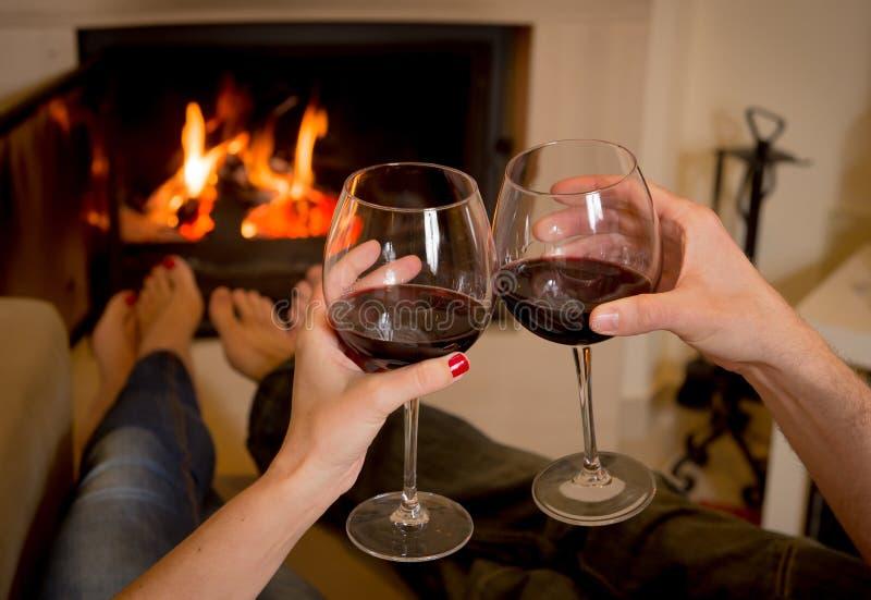 Paar het drinken wijn voor een brand royalty-vrije stock afbeelding
