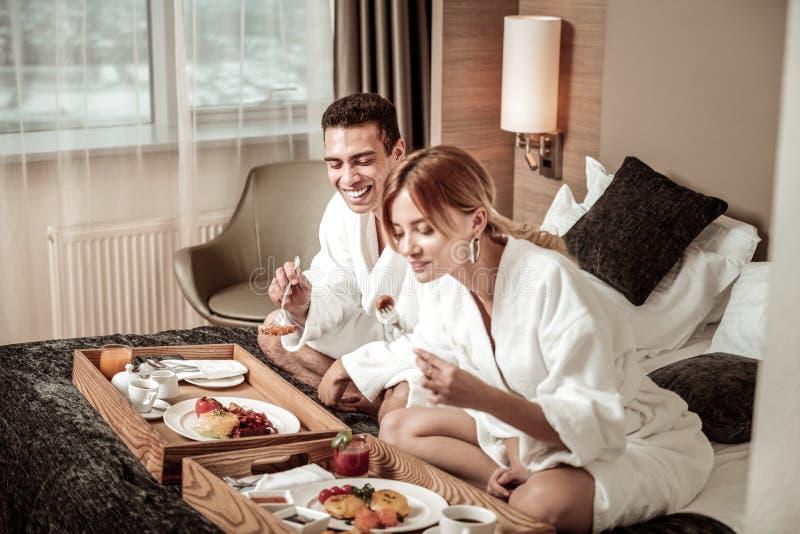 Paar het eten ontbijten en het lachen terwijl het planning van hun dag royalty-vrije stock foto