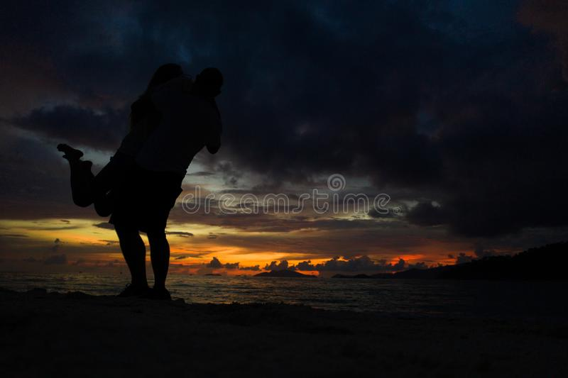 Paar het kussen op het strand met een mooie zonsondergang op achtergrond stock afbeelding