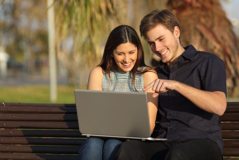 Paar het letten op media in een laptop zitting op een bank royalty-vrije stock afbeeldingen