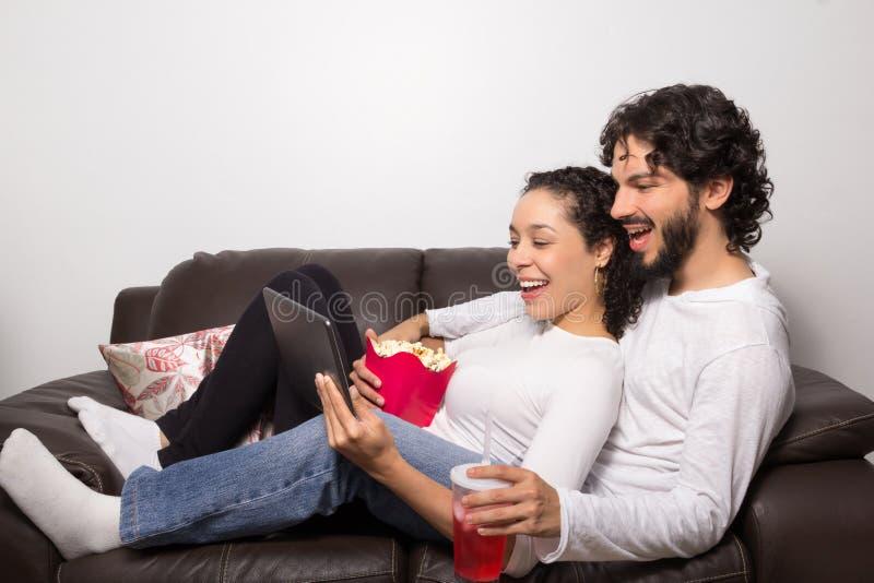 Paar het Letten op Video op Digitale Tablet Zij zijn gelukkig Relaxin royalty-vrije stock afbeelding