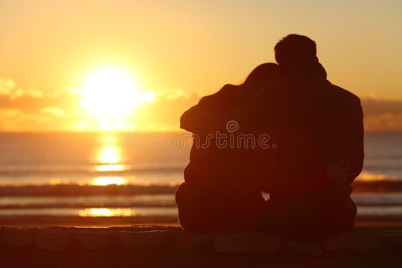 Paar het letten op zonsondergang op het strand in de winter stock afbeeldingen
