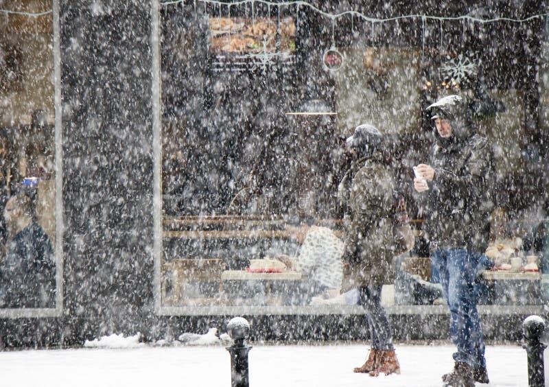 Paar het lopen stadsstraat in zware sneeuwval en mensen die in een restaurantvenster erachter eten royalty-vrije stock afbeeldingen