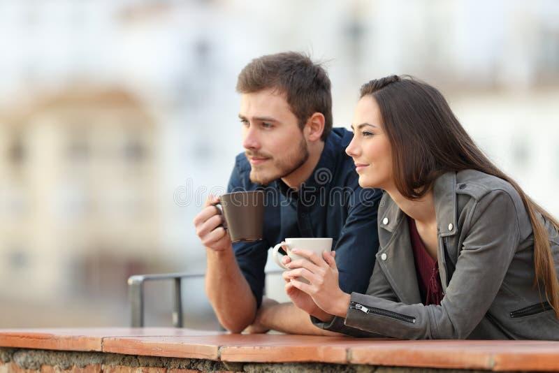 Paar het ontspannen het drinken koffie in een balkon op vakantie royalty-vrije stock foto