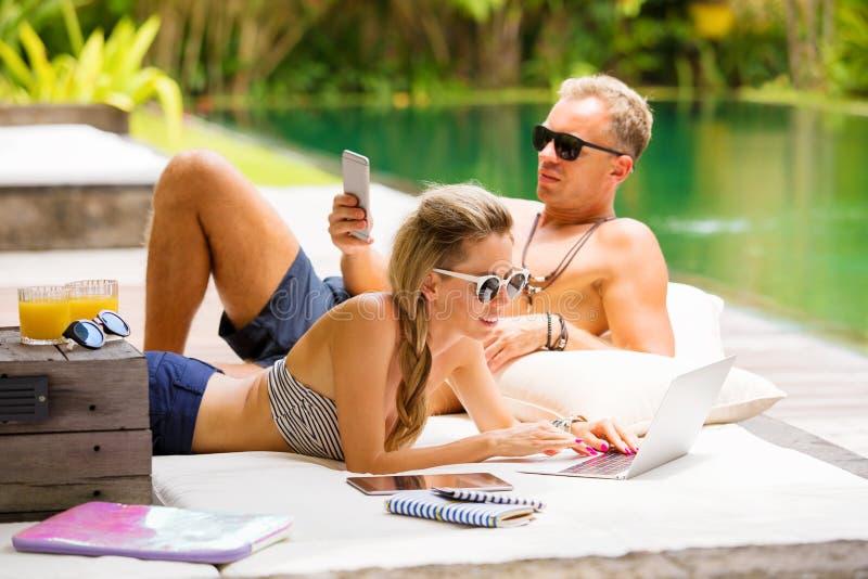Paar het ontspannen in hete de zomerdag en het gebruiken van technologie stock fotografie
