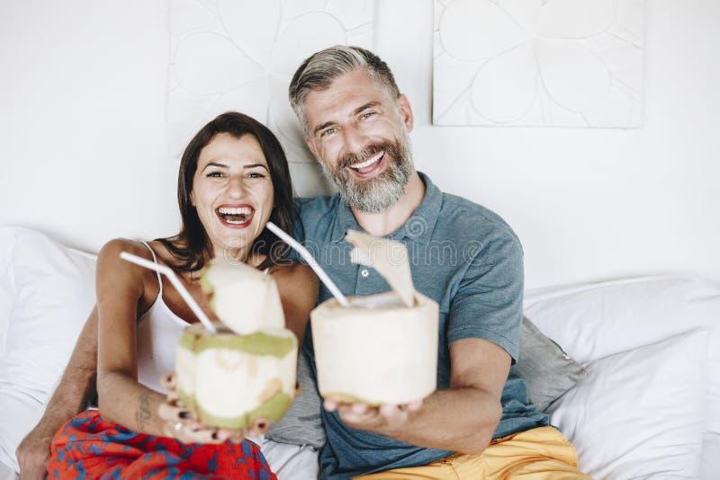 Paar het ontspannen op de bed het drinken kokosnoot stock afbeeldingen