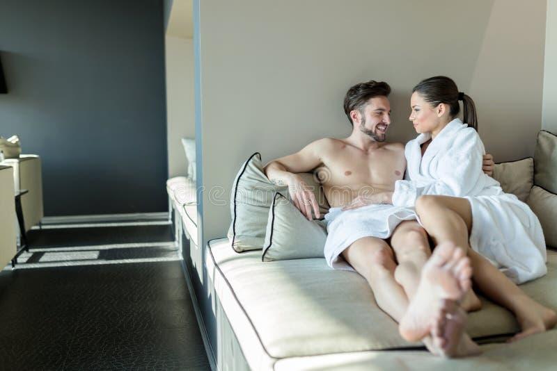 Paar het ontspannen op een wellnesscentrum, die in rob en een handdoek leggen royalty-vrije stock foto's