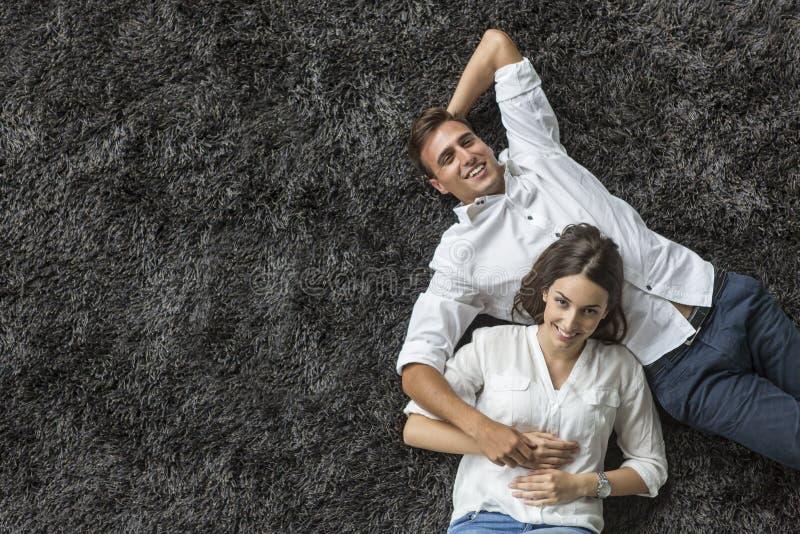 Paar het ontspannen op het tapijt stock afbeelding