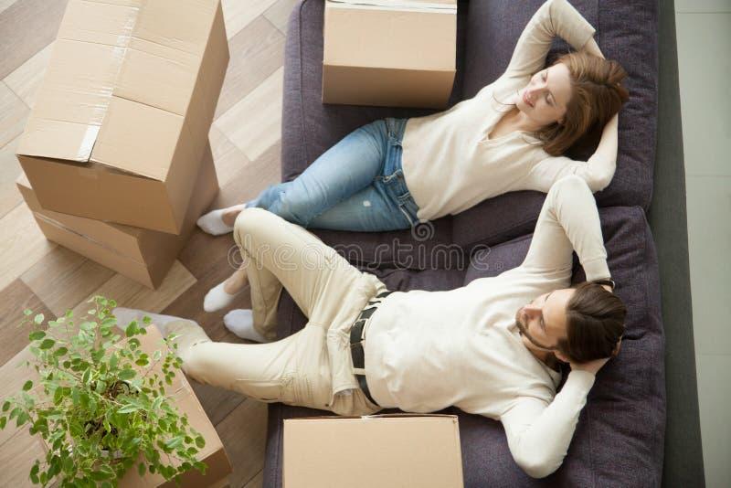 Paar het ontspannen op laag die zich in nieuw huis met dozen bewegen stock afbeelding