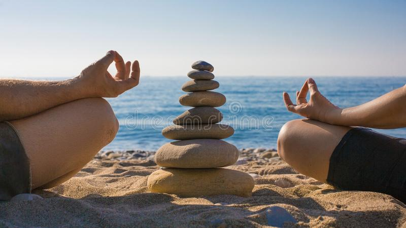 Paar het praktizeren yoga op het strand De rust en ontspant zen royalty-vrije stock foto's