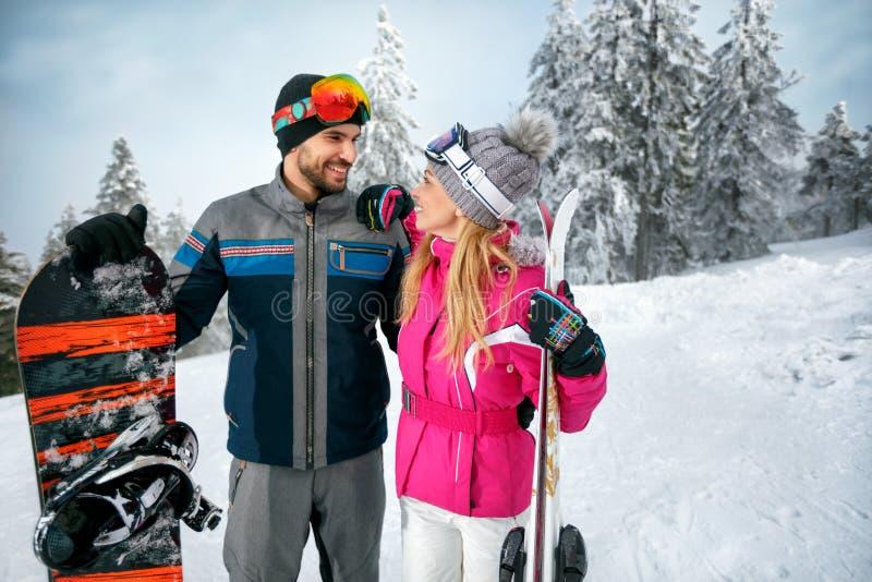 Paar het ski?ende en snowboarding genieten van in sneeuwbergen toget royalty-vrije stock foto's