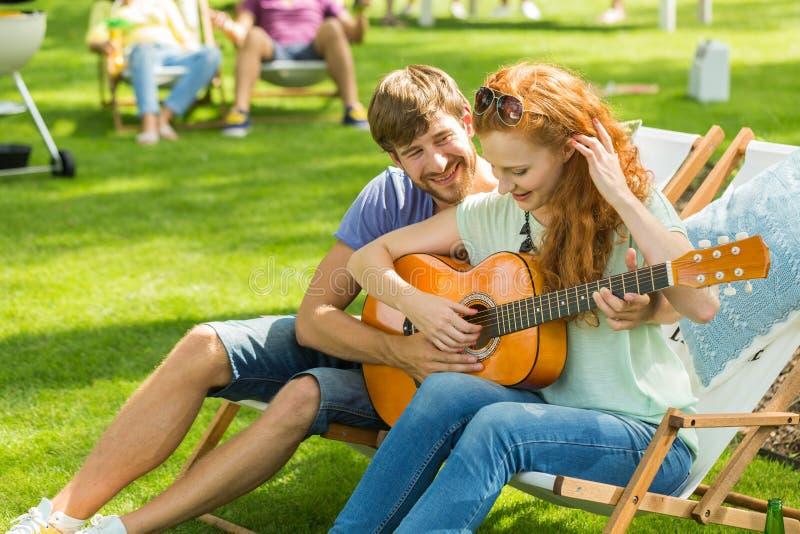 Paar het spelen gitaar bij kamp royalty-vrije stock foto