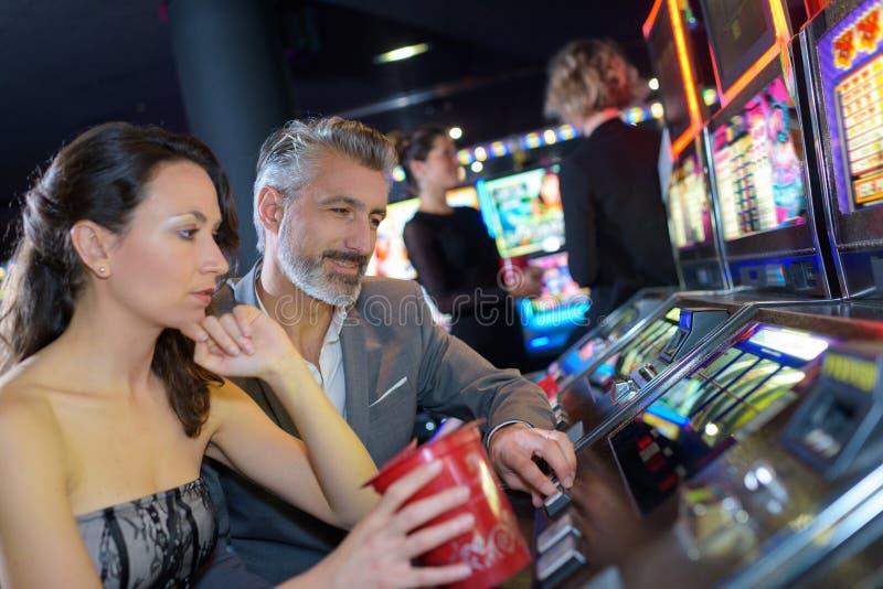 Paar het spelen gokautomaat in casino royalty-vrije stock fotografie