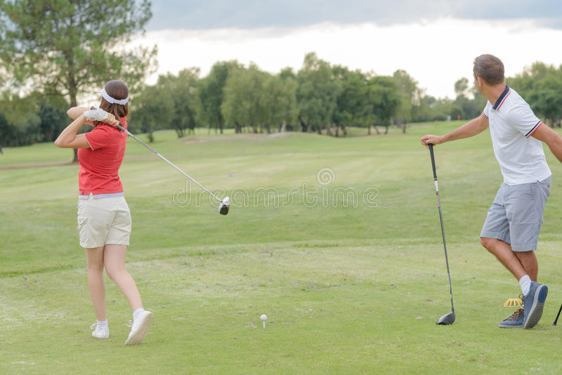 Paar het spelen om golf op groen stock afbeeldingen