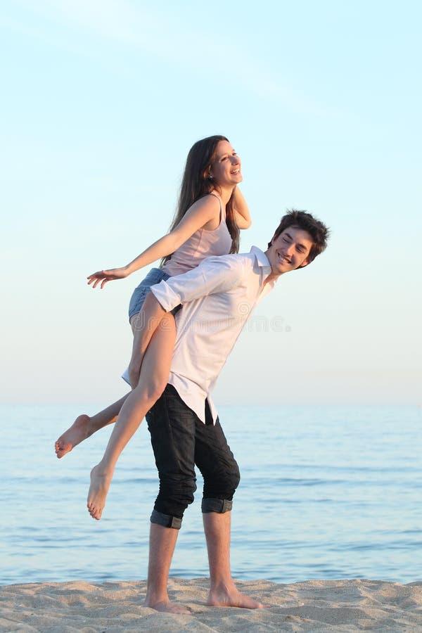 Paar het spelen op de rug op het strand stock afbeeldingen