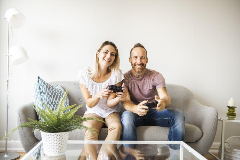 Paar het spelen videospelletjes die thuis, op bank zitten royalty-vrije stock fotografie