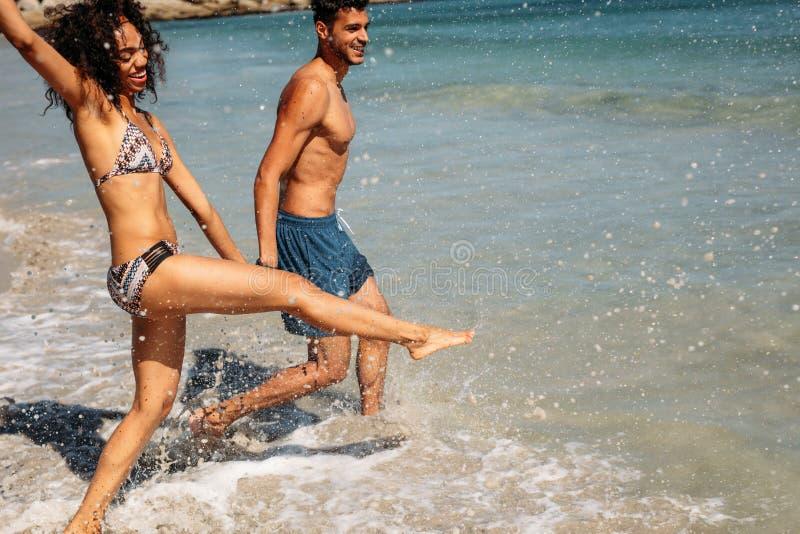 Paar het spelen in water op het strand royalty-vrije stock afbeeldingen