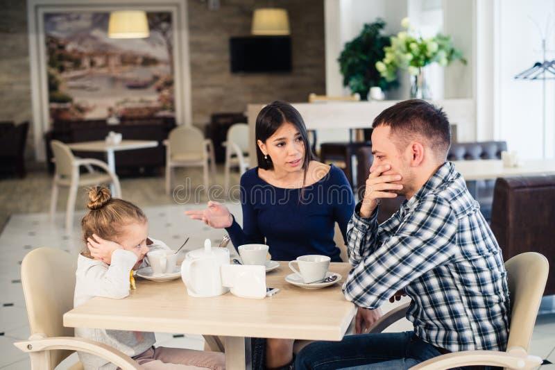 Paar het vechten voor kind bij koffie of restaurant stock fotografie