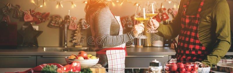 Paar het vieren Kerstmis in de keuken en drinkt wijn stock afbeeldingen