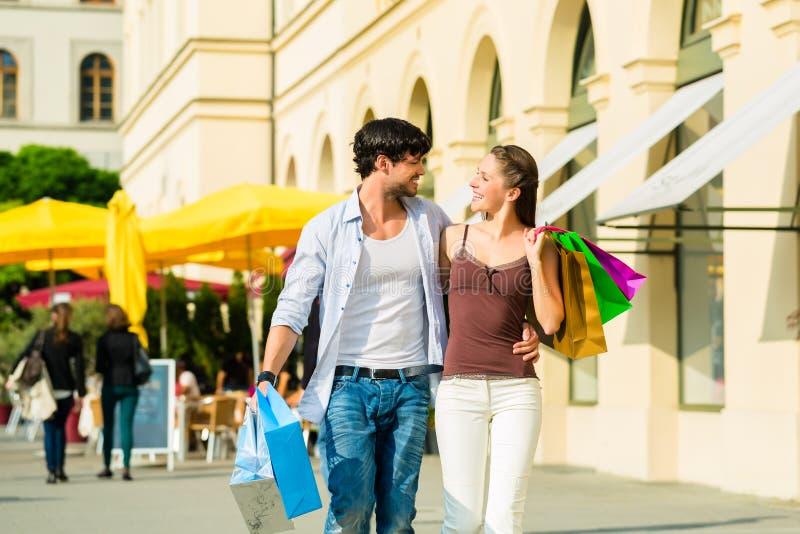 Paar het winkelen en zakgeld in stad stock foto